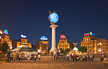Ukraine Kiev Place of Independence people tourists visitors sit on the place with view to building of neoclassic house of labor union right and column with the world globe iluminated place with historical buildings of sowjetic realismn architectur nationa