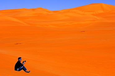 Woman sitting in the desert sand with a camera in her hand, Ubari Sand Sea, Sahara, Libya, Africa