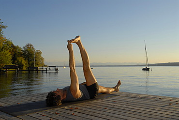 Man doing yoga on a wooden pier by a lake