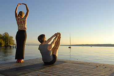 Woman and man doing yoga on a wooden pier by a lake