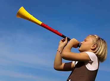 8-year-old girl blowing a trumpet in the colours of the German flag, black, red and gold, Germany