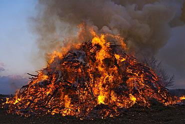 Easter eve bonfire burning at dusk, Germany