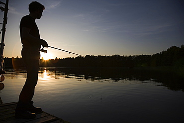 A man fishing in the evening from a dock in a lake