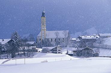 Snow falling over St. Nicholas Church, Pfronten, East Allgaeu, Bavaria, Germany, Europe