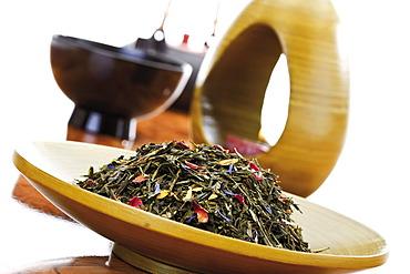 Green tea mixture in a wooden bowl and an Asian tea set
