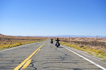 Two motorcyclists on a highway between Utah and Arizona, USA