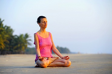 Woman meditating on a beach in the evening, Kerala, India