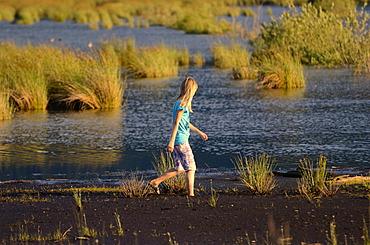 Girl wading in a wet bog, Stammbecken Moor, former Nicklheim peat works, Rosenheim, Bavaria, Germany, Europe