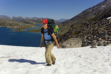 Young woman hiking, backpacking, hiker with backpack, snow field, descending towards summit of historic Chilkoot Trail, Chilkoot Pass, Crater Lake behind, alpine tundra, Yukon Territory, British Columbia, B. C., Canada