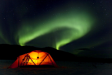 Illuminated expedition tent and traditional wooden snow shoes, Northern Lights, Polar Lights, Aurora Borealis, green, near Whitehorse, Yukon Territory, Canada