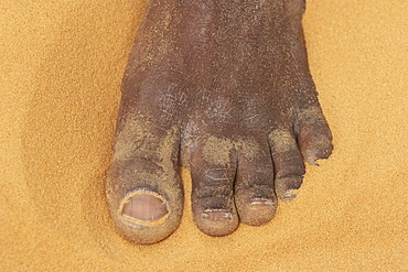 Foot and toes of a man in sand