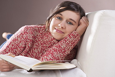 Girl relaxing on a sofa with a book