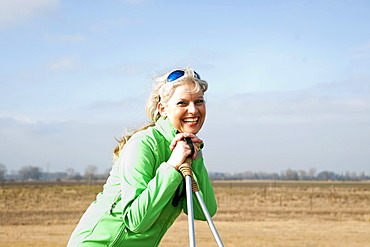 Smiling woman doing Nordic walking