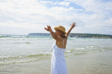 Woman standing with her arms outstretched on a beach