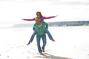 Man carrying a woman piggyback on a beach