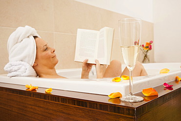 Woman taking a bath and reading a book