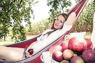 Pregnant woman in a hammock in the apple garden