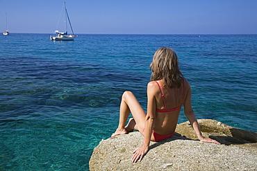 Woman sunbathing on a rock, Spiaggia di San Andrea, Elba, Italy, Europe