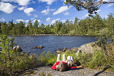 Mother and daughter resting on a big rock at St. Hindsjoen lake near Alsterbro, South Sweden, Scandinavia, Europe