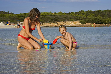 Mother and child playing at beach, Cala Brandinchi, Sardinia, Italy