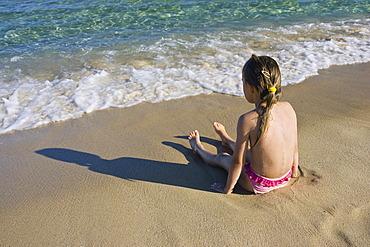 Little girl sitting at the beach, Sardinia, Italy