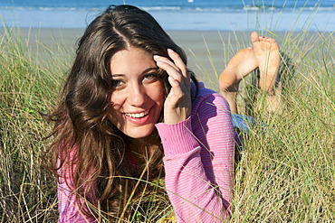 Young woman lying in the dunes on the beach, Brittany region, France, Europe