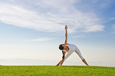 Young woman practising Hatha yoga, here the pose utthita parshvakonasana, side stretch