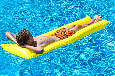 Boy, 12 years, lying on a lilo in a swimming pool