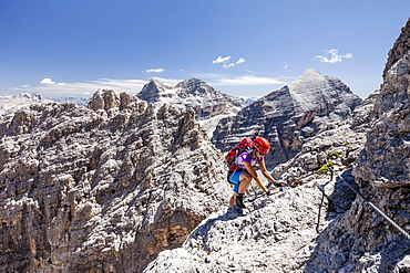 Climber, descent from the Southern Fanesspitze on the Via ferrata Tomaselli, behind the Tofana di Rozes, Tofana di Mezzo and Tofana di Dentro, Dolomites, Alps, Province of Belluno, Italy, Europe