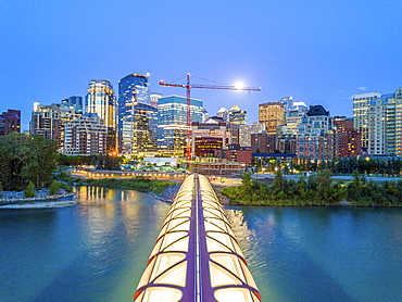 Calgary downtown at dusk with iluminated Peace Bridge and full moon, Alberta, Canada, North America (Drone)