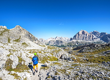 Hiker with climbing helmet on footpath to the Nuvolau, view of the Nuvolau summit and mountain range Tofane, Dolomites, South Tyrol, Trentino-Alto Adige, Italy, Europe