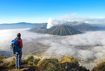 Young man in front of volcanic landscape, view in Tengger Caldera, smoking volcano Gunung Bromo, in front Mt. Batok, behind Mt. Kursi, Mt. Gunung Semeru, National Park Bromo-Tengger-Semeru, Java, Indonesia, Asia