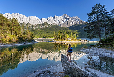 Hiker stands on rocks, looks into the distance, Lake Eibsee lake and Zugspitze, Wetterstein range, near Grainau, Upper Bavaria, Bavaria, Germany, Europe