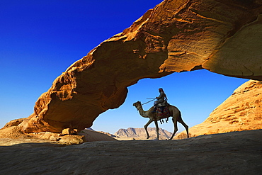 Bedouin rides his camel, Rock-Arch Al Kharza, Wadi Rum, Jordan, Asia