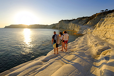 Tourists during sunset, rocky coast of Scala dei Turchi, limestone rocks, Realmonte, Province of Agrigento, Sicily, Italy, Europe