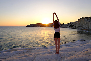 Young woman during sunset, rocky coast of Scala dei Turchi, limestone rocks, Realmonte, Province of Agrigento, Sicily, Italy, Europe