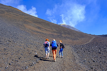 Hikers climbing through volcanic landscape, Volcano Etna, Province of Catania, Silzilia, Italy, Europe