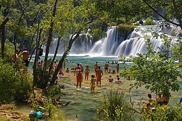 Tourists bathe at the waterfall Smotorcycleinski Buk, National Park Krka, Sibenik-Knin, Dalmatia, Croatia, Europe