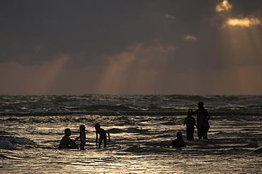 People in backlight in water, rays of sunlight, dark clouds over sea, Beruwela, Western Province, Sri Lanka, Asia