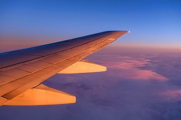 Wing of a plane, flight over clouds, dusk, sunset, Norway, Europe