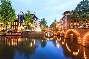 Bikes, boats, canal and charming architecture at dusk, Amsterdam, Netherlands
