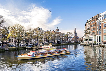 touristic boat on channel, back Mint tower, Amsterdam, Netherlands