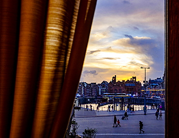 View of the station forecourt through a window with curtain, evening, Amsterdam, The Netherlands, Europe