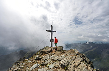 Hiker at the summit cross of Hochgolling, Schladminger Höhenweg, Schladminger Tauern, Schladming, Styria, Austria, Europe