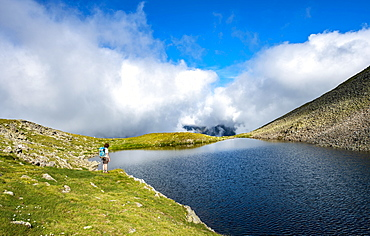 Hiker at Sattelsee lake at Greifenbergsattel, ascent to Greifenberg, Schladminger Höhenweg, Schladminger Tauern, Schladming, Styria, Austria, Europe