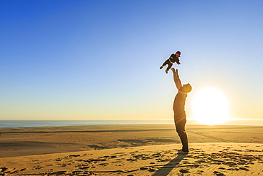 Father throws his little laughing son in the air, sandy beach, Langstrand, Namib Desert, Swakopmund, Erongo Region, Namibia, Africa