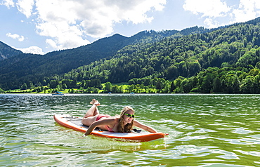 Young woman lying on a Standup-Paddle Board or SUP, paddling with hands in the lake, Schliersee, Upper Bavaria, Bavaria, Germany, Europe