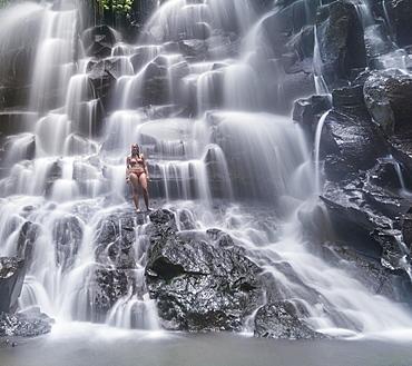 Woman standing in waterfall, Air Terjun Kanto Lampo, near Ubud, Bali, Indonesia, Asia