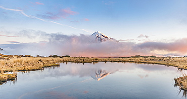 Reflection in Puakai Tarn, stratovolcano Mount Taranaki or Mount Egmont at sunset, Egmont National Park, Taranaki, New Zealand, Oceania