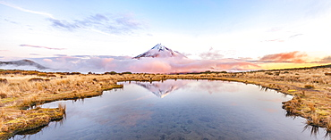Reflection in Pouakai  Tarn lake, pink clouds around stratovolcano Mount Taranaki or Mount Egmont at sunset, Egmont National Park, Taranaki, New Zealand, Oceania